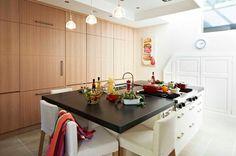 cuisine avec îlot central, plans de travail en granit noir, façades laquées blanc, table de cuisson Viking et évier inox, mur de rangement façade oberflex, cellier et réfrigérateur intégré