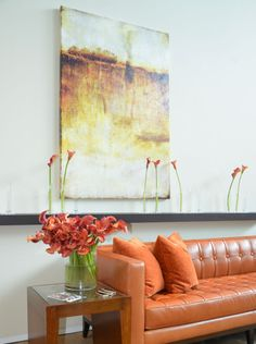 Contemporary seating area. LOVE orange as an accent color. Love the painting and the modern leather sofa | Design Magnifique