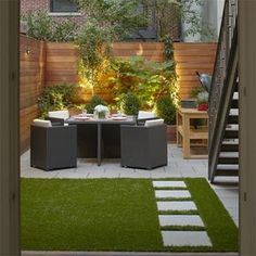 This once bare courtyard and tiny garden are transformed into a stunning outside dining area that also provides plenty of space for entertaining. Artificial turf provides a lovely bed of green in this shady area.