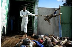 AFP PICTURE OF THE YEAR 2010 A man throws a dead body at the morgue of the general hospital, January 15, 2010 at Port Au Prince following the 7.0-magnitude quake on January 12. More than 50,000 people were killed and 250,000 injured by this week's earthquake, which also left nearly 1.5 million homeless, a Haitian minister said. After three days of Haitians being left to fend mostly for themselves in one of the world's poorest countries.  Photograph by: OLIVIER LABAN-MATTEI, AFP/Getty Images