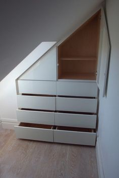 The loft storage unit was designed and made to make use of the awkward space that you sometimes find with loft conversions. In this case we built a bespoke unit containing drawers and cupboards in birch plywood with touch opening runners and latches and clad it all in white glass to achieve a minimal contemporary aesthetic.
