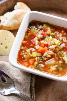 bowl of barley soup in bowl with side of cheese and bread