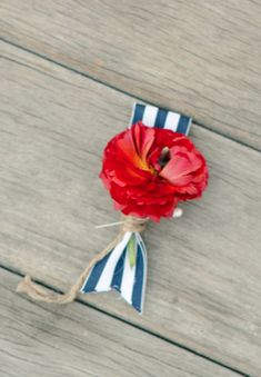 Easy boutonniere for a nautical themed wedding with a small red flower