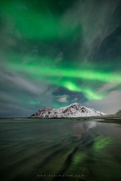 Hustind Wavelengths... The majestic Mount Hustind stands proud between a spectacular Auroral display above, and wonderful ripple patterns below, reflecting the lights by Erez Marom on 500px.