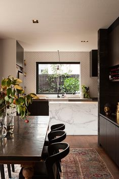 love the contrast of the white island counter against the rest of the dark wood kitchen