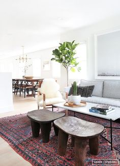 Living room with rustic vibe, gray sofa, white walls, rustic wooden antique stools, persian rug with blue and red accents