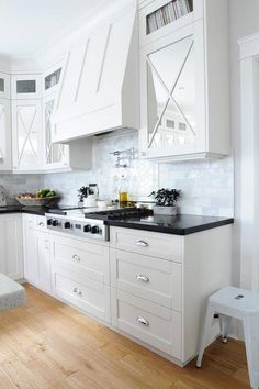 Black and white kitchen features mirrored upper cabinets with x trim and white shaker lower cabinets paired with black quartz countertops and a marble tiled backsplash.