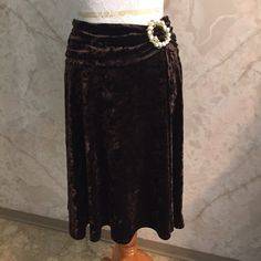 """Brown Velvet Slip On Skirt w/Pearl & Gold Details This is such a pretty slip on skirt. Made by Just in Time, this is a stretchy and velvety chocolate brown size medium skirt. It's made from polyester and spandex. Length is about 23"""". The sides of the waist are gathered and have a really cute look to them. There's a cute petal and gold circle deco on the one side. Just In Time Skirts Midi"""