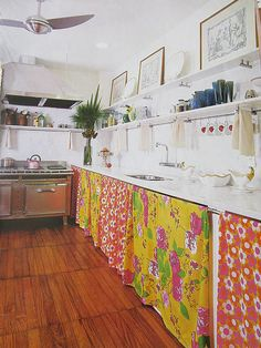 Use sheets of fabric instead of cabinet doors to conceal things inside the cabinet - great way to add some pizzazz to any kitchen!