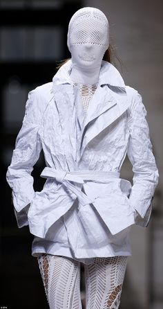 A model takes to the runway in a creased blazer-like jacket and vision-restricting mesh ma. Look Fashion, Fashion Brand, Fashion Show, Paris Fashion, Crochet Jumpsuits, Military Style Jackets, Tailored Jacket, Modern Outfits, Sheer Dress