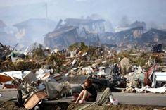 Mulher sentada em meio aos destroços causados por um forte terremoto e subsequente Tsunami em Natori, Japão, em março de 2011