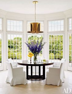 White-slipcovered chairs ring a modern table in the bright breakfast area of Tommy Mottola and Thalia's Connecticut home.