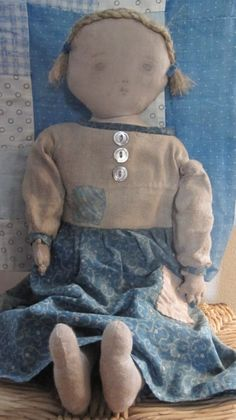 """This doll is just precious!  I put so much work into her dress…just love her!  Her hair is braided flax.  The early, blue calico in her dress is so lovely.  She is stitched entirely by hand and stuffed with early rags.  She is 18"""" tall.  A signed and dated Fat Hen Farm original."""