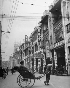 Rickshaws on a street in Canton. Photograph by Carl Mydans. Canton, China, March 1949.