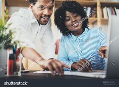 Two young coworkers working together in a modern office.Black business partners discussing new startup project.Horizontal,blurred