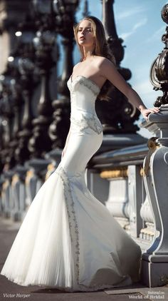 Strapless, fit and flare gown with a beaded bodice and train. Tulle godet on front skirt.