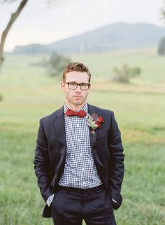 Groom style: Charcoal gray suit, gingham shirt and red bow tie. Image by Elisa Bricker. See more in the Winter 2014 issue of Weddings Unveiled: www.weddingsunveiledmagazine.com.