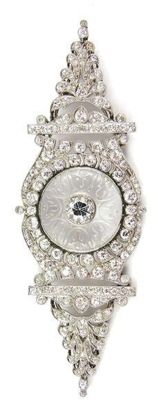 Early 20th century diamond and rock crystal brooch by Cartier, c.1915, of navette shaped outline, centred by a carved rock crystal circular panel, inset with a principal round brilliant cut diamond, to a pierced and millegrain set foliate cluster frame formed by a cartouche with elongated anthemion either side, set throughout with round cut diamonds, rubbed serial number possibly 725  Length 8.7cm / 3 3/8''  Weight: 19g