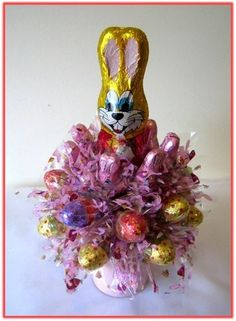 A chocolate Bunny surrounded with 21pcs of Easter character milk chocolates and eggs, adorned with colourful cellophane, nested in a pink Easter bucket. A lovely Easter gift!