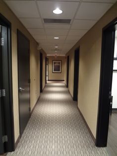 (DS - maybe dark doors like this are good?) Hallway of medical office with carpet, custom stained oak doors and recessed can lighting Office Door, Hallway Decorating, Office Renovation, Office Carpet, Commercial Carpet, Office Space, Medical Decor, Medical Office Decor, Office Design