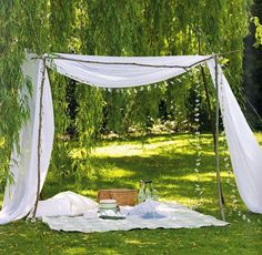 A makeshift picnic tent with branches and fabric