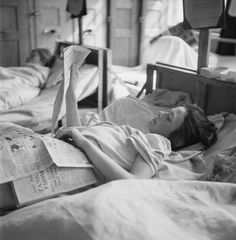 THE LIBERATION OF BERGEN-BELSEN CONCENTRATION CAMP, MAY 1945. For the first time in four years, a young Czech girl and former camp inmate is able to read a newspaper while recovering in the hospital set up in Hohne Military Barracks nearby.