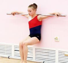 肩にバーベルを乗せて空気椅子の体勢のまま長時間じっと耐える特訓中の体操少女