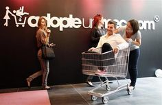 A single woman pushes a bachelor who rides in a shopping trolley at the 'adopt-a-guy' (adopte-un-mec) store in Paris September 12, 2012. The boutique, with a short-term lease which expires at the end of the week, opened its doors, promising a high-end shopping experience for women searching for Mr Right. REUTERS-Jacky Naegelen