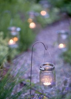 Light the way - Canning jars with tea lights create a sparkling entrance to any outdoor gathering. Wrap the tops of lidless jars with hose clamps and suspend from a tree branch or a shepherd's-crook stake. I would use insulators instead of Mason jars. Backyard Lighting, Outdoor Lighting, Garden Lighting Ideas, Outside Lighting Ideas, Outdoor Table Decor, Outdoor Candles, Outdoor Ideas, Deco Nature, Floating Candles