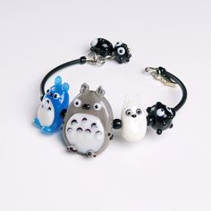This Totoro family lampwork bracelet is so cute and adorable! Artist lampwork beads are made by me, one by one in a lampwork technique. This glass is rather durable as it is put in a very high temperature after the bead is made. Its very tender and unique!  Set: https://www.etsy.com/listing/254914236/grey-totoro-lampwork-pendant-kawaii?ref=shop_home_active_11 https://www.etsy.com/listing/254817245/totoro-family-lampwork-earrings-soot?ref...
