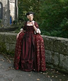 my 18thc robe a la francais front view.Its made from shot faux silk embrioded with flowers .Theres at least 10 yards of fabirc in the dress and trims . the petticoat is made from shot red black sil...