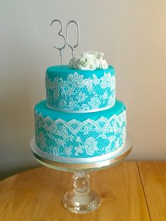 Two tier blue/turquoise cake with edible cake lace and sugarpaste white flowers.