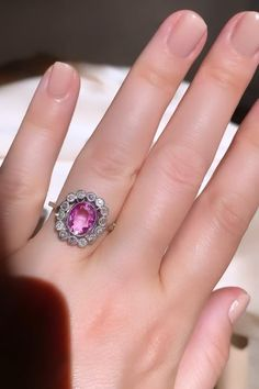 Edwardian ring centering an approx. 1.75 carat oval-cut pink sapphire in an old European-cut surround of approx. 0.60 carat, mounted in millegrain platinum. With French importation mark. Center: 15.1 x 14mm, band: 1.4-1.5mm. Circa 1915