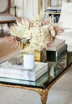 A bold geometric vase plays off the stylized leaflike motif along the gilded coffee table.