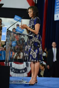 Mrs. O is wearing a royal blue, grey and black floral print dress accessorized with an Erickson Beamon floral pin at the neck.