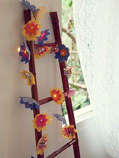 Com as bordas recortadas, forminhas para cupcake e docinhos de diferentes tamanhos compõem flores multicoloridas. Escada Villa Pano