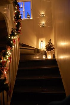 Candles in lanterns on the floor . i want a stair case one day like that i can decorate