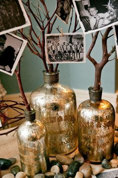 Glass jars/bottles (shades of Blue) with branches and pictures cloths pined to... For center pieces... then have sand, shells and stones around the bottem