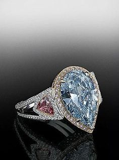 Fancy deep blue pear shaped diamond set in pink pave frame with fancy pink side stones.