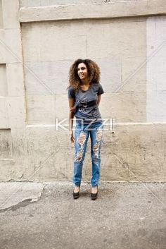 laughing portrait of a young woman - A portrait that shows the concrete wall and a young, smiling woman's surroundings as she stands casually.   MUA - Wright Artistry