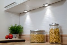 Discreet under cabinet spot lights add task lighting as well as interest to the kitchen design