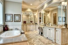 Luxurious Master Bathroom with travertine tile floor with mosaic inlay, hand glazed antiqued custom cabinetry, separate tub and shower, two large walk-in closets and built-in cabinets.