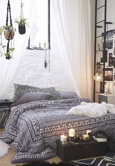 Bohemian bedroom with black and white textiles. Urban Outfitters. I like the short table at the foot of the bed