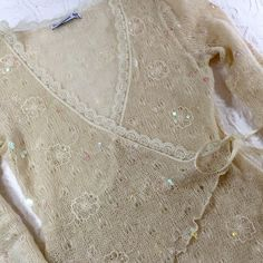 Sparkle Knit Wrap Sweater  Size: Small Semi-sheer cream knit Vertigo Paris wrap sparkle sweater. Like new. Worn once. Just discovered a few tiny dots on one ribbon so I'm pricing to reflect this. I never saw this. Totally feminine. Subtle sparkle in the randomly scattered sequins. Vertigo Paris Sweaters