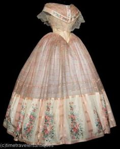 Ball gown, early 1860's from a past ebay auction (Time Travelers Antiques) listed circa 1864, but I think that's latest possible date. Ball gown styles don't change too much until 1865-6 with the new straight waists, tiny sleeves, and elliptical skirts. This bodice with the deep pointed waist and very wide berth could easily be from 1860. The combination of pink windowpane sheer silk with the band of printed silk is amazing. The berth is trimmed with expensive bobbin lace. Info from Hither…