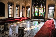 Reception room inside Beiteddine Palace in Lebanon. It features stained glass windows & generous built-in banquette seating across the length of the room.