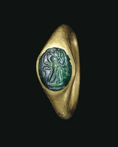 A ROMAN GOLD AND GREEN CHALCEDONY FINGER RING CIRCA 1ST-2ND CENTURY A.D. The plain hoop round in section, expanding at the shoulders to the oval bezel, set with a slightly convex oval green chalcedony engraved with a muse striding forward, holding a kithara, framed by billowing drapery