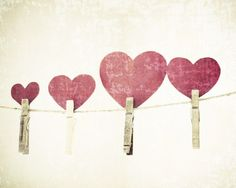Red paper hearts on a clothes line with clothes pins, softly textured with a vintage feel.