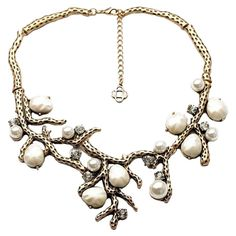 Striking necklace, showcasing an organic silhouette accented by faux pearls.
