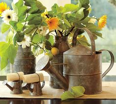 Flowers in old tin watering cans and milk cans. What a great idea for a garden party!!